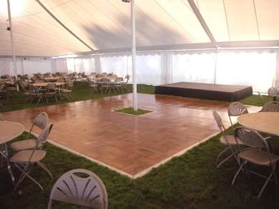 White high peak party tent with dance floor, stage, table and chair rentals set up in Madison Wisconsin