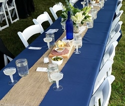 Banquet table with blue tablecloth and place settings